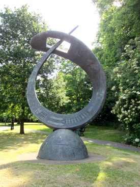 A metal sculpture like a giant needle curved round so the sharp end goes through the eye towards the sky | Anne Langley