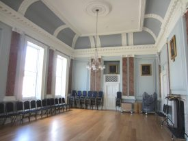 Room with wooden floor, 'marble' pilasters, chandelier and plaster ceiling   Image courtesy of Anne Langley