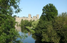 Warwick Castle from the bridge. Trees in front of the river. | Photo by Richard Neale.