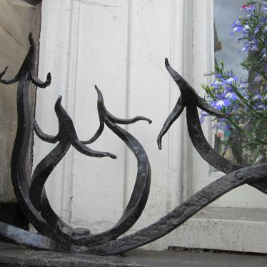 Arrow shaped wrought iron spikes on window ledge with white-painted window and lobelia behind | Anne Langley