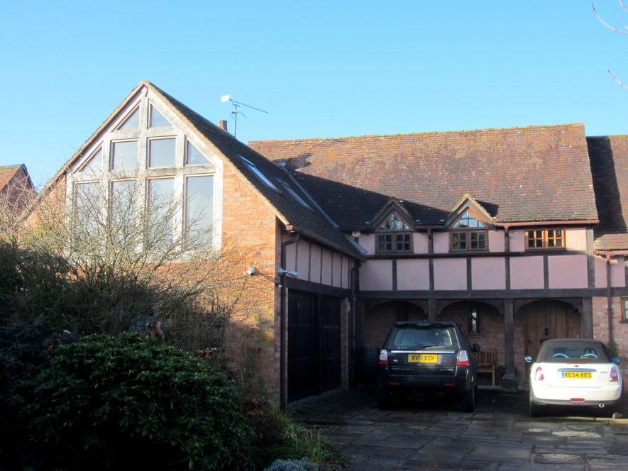L-shaped tiled brick building with (modern) timber-framing and pink plasterwork on the upper storey   Anne Langley