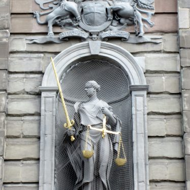 Justice with a blindfold, gilded scales and sword in a niche surmounted by a coat of arms | Anne Langley