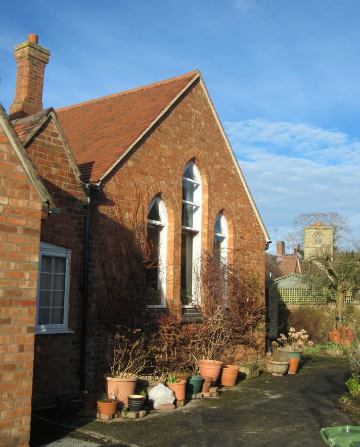 Red brick one storey building with triple arched windows and tiled roof | Anne Langley