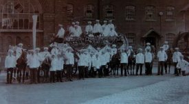 Bakers' entry in the Coventry Carnival 1907. Taken outside Robbins and Powers Flour Mills in Wheatley Street which shows how many bakers there were in the city at that time! The large white mark on the left hand side of the photograph is a bag which was held up to bedroom windows to collect cash! The display on the side of cart says 'Your Daily Bread' made from bread. Little Alf is the 3rd boy on the right from the bag. | Image supplied by Doris Pails.