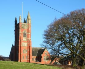 Bright red brick building with stone dressings; tower with pinnacles and flagpole | Anne Langley