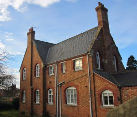Red brick 2-storey building with slate roof and arched windows painted white | Anne Langley