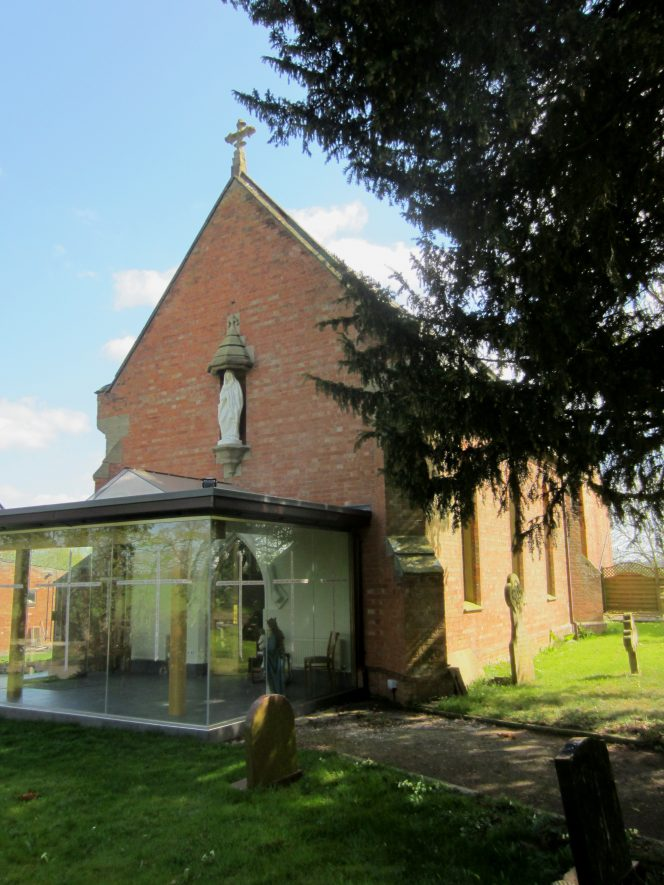 Red brick church with stone dressings. White statue in niche and modern glass porch. Churchyard in foreground. | Anne Langley