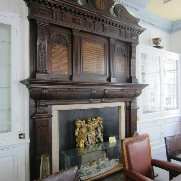 Carved wooden overmantel with gold inscription; coat of arms in fireplace and chairs around a board table | Anne Langley