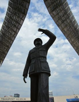 Statue of Sir Frank in RAF uniform looking up into the sky below two huge arches | Anne Langley