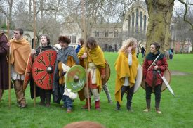 People in Viking costume with pikes and shields on a green beside a church | Wendy Joyner