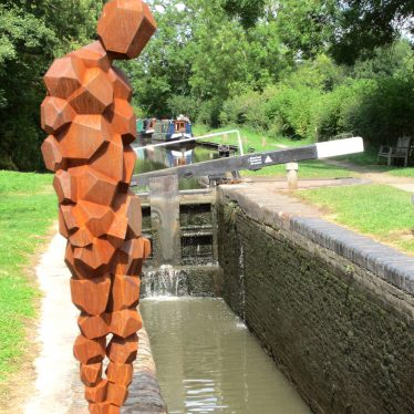 Iron man looking down into a canal lock (lock gate and narrow boats in the distance). | Anne Langley