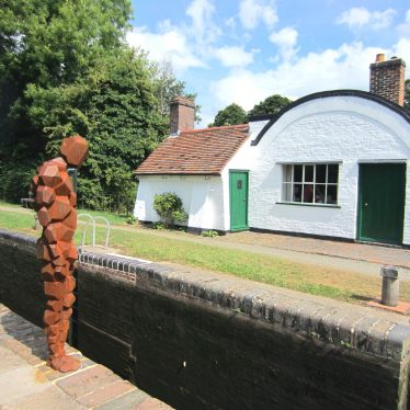 Iron man looking down into lock. One-storey white-washed cottage with barrel-shaped roof. | Anne Langley