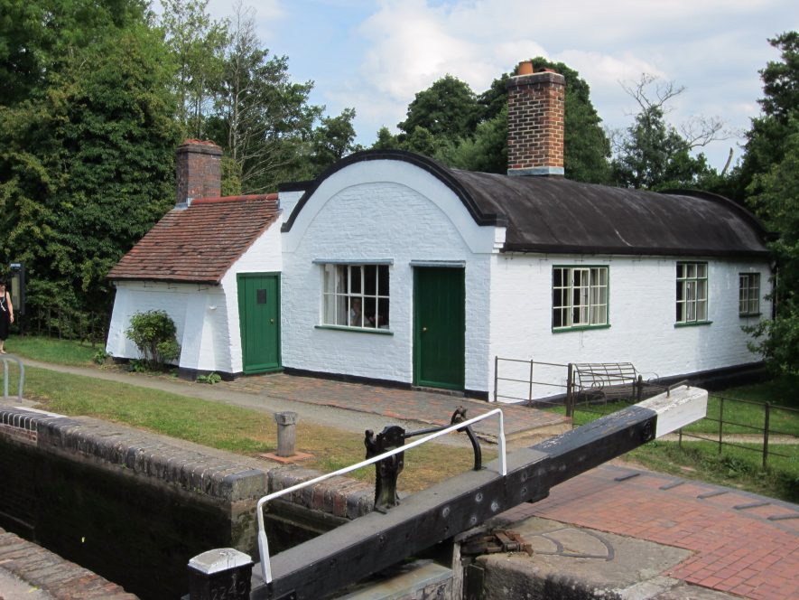 One-storey whitewashed cottage with barrel-shaped roof and small extension beside lock with gate & towpath | Anne Langley