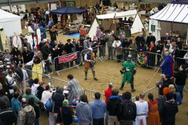 Two people in armour fighting with swords and shields in a square arena surrounded by spectators, stalls etc. | David Smith from NLHF