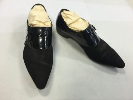 Pair of black pointed shoes with patent leather around the top and side lacing. | Warwickshire Museums.