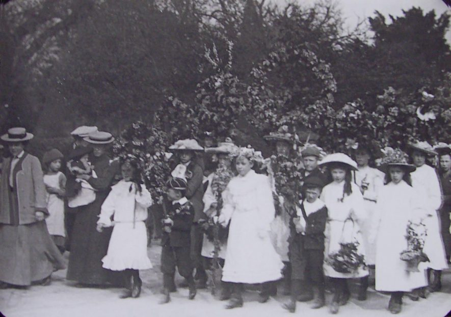 May Day Celebrations in Brailes. Several adults and children with garlands of flowers and wearing boaters, some decorated with flowers. | Warwickshire County Record Office reference PH1035/B5193.