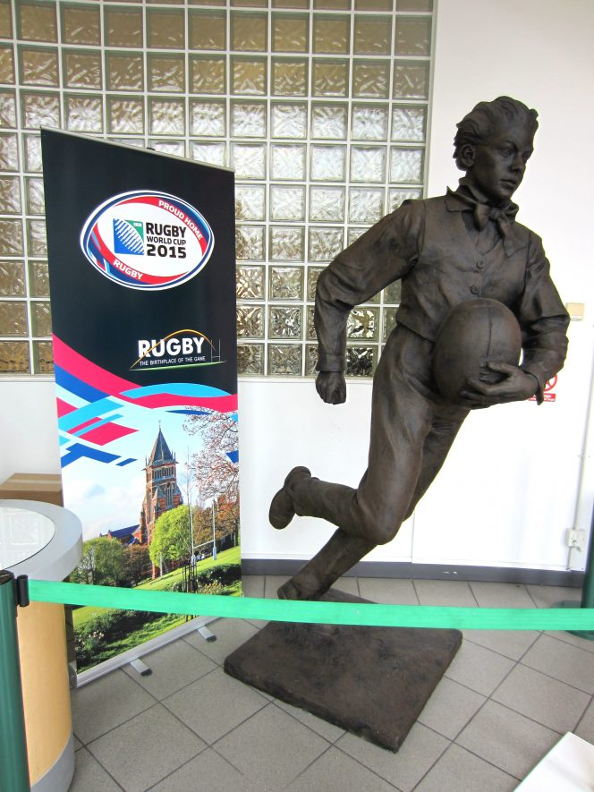 Statue of a boy with a bow tie clasping a football and running fast | Anne Langley