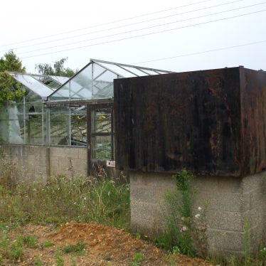 Brandon Garden Centre. A greenhouse and water tank. The water tank is rusting away. | Photo by Rob Woodgate.