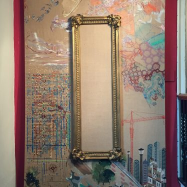 Gilt frame surrounded by tapestry work in pink blue and purple of planets, a street scene etc | Photo courtesy of Olivia Hewkin