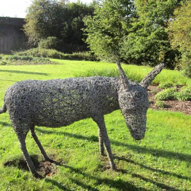Woven wire sculpture in a green field with railway line behind   Anne Langley