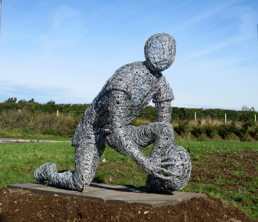 Wound wire sculpture of a player placing a rugby ball on the ground | Anne Langley