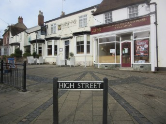 High Street, Kenilworth, 2015. The sign is in sharp focus at the front, shops behind.