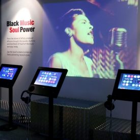 International Slavery Museum. The screen behind says Black Music Soul power, as a woman sings into a 50s style microphone. | Image courtesy of Redman Design.