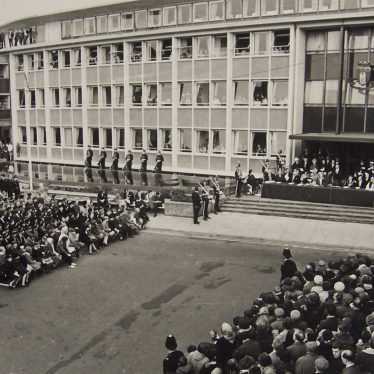 Staff lean out of their office windows to catch a glimpse of the Queen Mother. | Warwickshire County Record Office reference PH143/1155