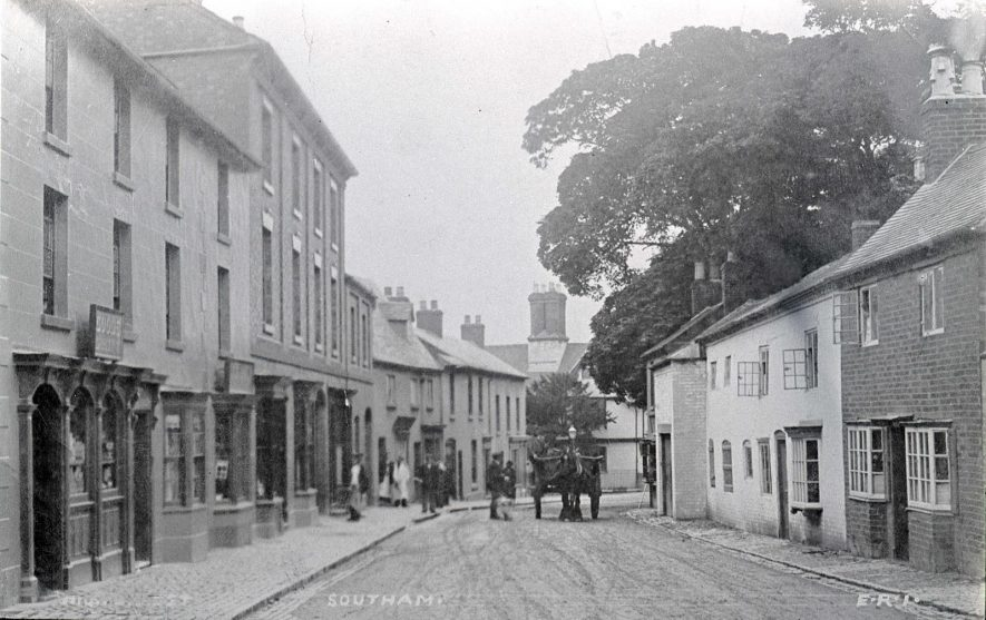 High Street, Southam. A horse and cart is in the centre of the road, a man wearing a cap is talking to the driver. | Photo courtesy of Southam Heritage Collection