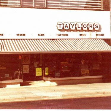 Shop front with awning of the Taylors of Nuneaton advertising pianos, organs, radio, TV, music and records. | Picture courtesy of Nuneaton Memories