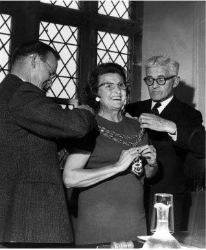 Florence Adcock, first lady Mayor of Kenilworth in 1979, surrounded by two councillors adjusting her chain of office.