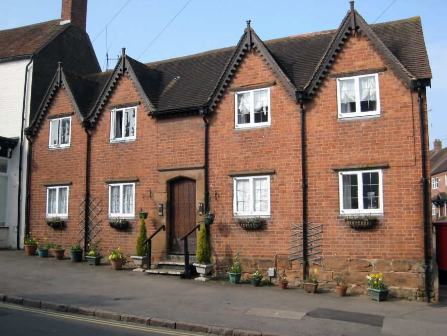 Row of 4 units 2-storey brick with tiled roof & gables. Central entrance up steps for all 4 | Anne Langley