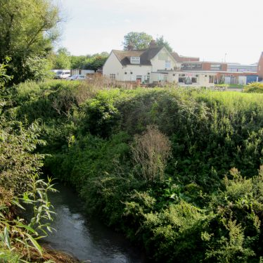 River in foreground, cream-painted building in the background with tiled roof | Anne Langley