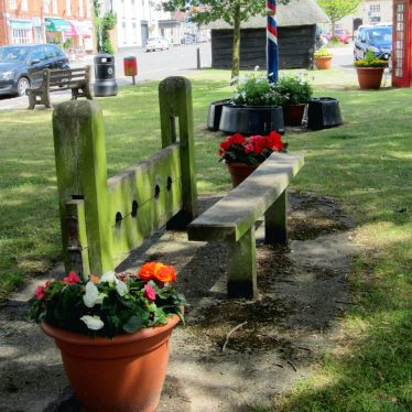 Stocks with 4 holes & bench. Base of maypole, bus shelter and phone box behind. | Anne Langley