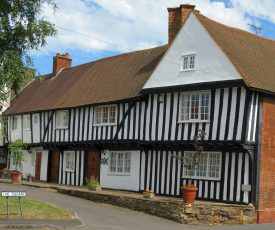Black & white timber framed house; with jetted 2nd storey & tiled roof; attic window in gable and brick side wall | Anne Langley