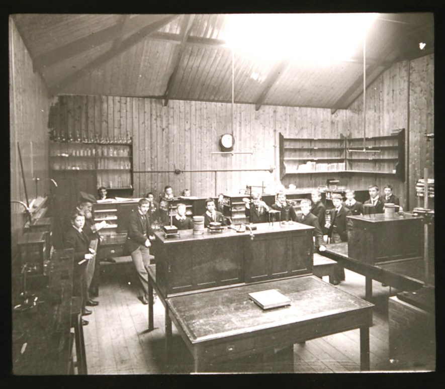 Classroom with benches and scientific equipment; boys and master; shelves of glassware behind; gas lighting | Courtesy of Warwickshire CC, Rugby Library Local Studies Collection; WCRO PH827/5/15; photographer Rev. E. Dew