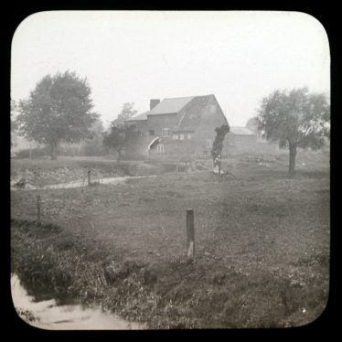 River, field and trees in foreground, mill buildings in the background | Courtesy of Warwickshire CC, Rugby Library Local Studies Collection; WCRO PH827/5/24; photographer Rev. E. Dew