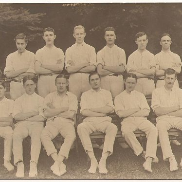 photographed by George Redding. they are sat in two rows in cricket whites, with a man in a suit either side of the back row. | Image courtesy of Alistair Redding.