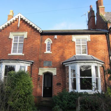Red brick 2-storey house with 2 bay windows and bronze plaque over the door | Anne Langley