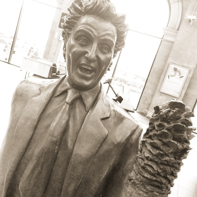 Ken Dodd statue at Liverpool Lime Street. A close up of the bronze, with Dodd's typical tickling stick in front.   Image originally by  Ewan McIntosh and uploaded to Flickr under the CC BY-NC 2.0 license.