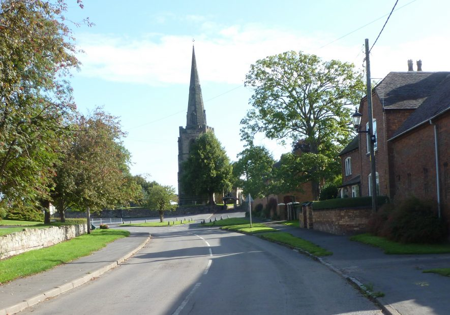 A view looking up the main road with the church, with spire, in Newton Regis. | Caroline Smedley