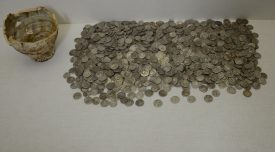 The South Warwickshire Hoard. A number of coins on a white surface, with a broken cup on the left hand side. | Photo courtesy of Sara Wear, Warwickshire Museum