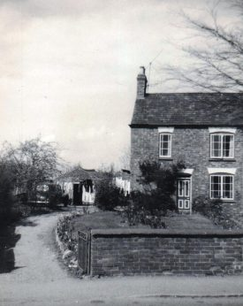 11 Main Street, Clifton on Dunsmore in 1955. A black and white end terrace house, with a brick wall in front. | Family photograph courtesy of Linda Doyle (Brockbank)