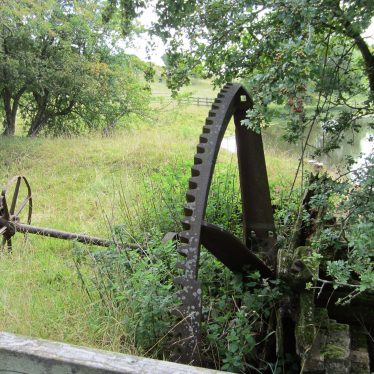 Remnants of machinery from King's Newnham mill.Axle and cogwheels lying by a river | Image courtesy of Anne Langley