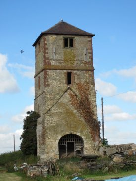 Square stone tower with brick dressings; windows in tower and arched entrance below rising from farmyard | Anne Langley