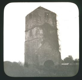 Square stone tower with ivy growing up it; windows in tower and and arched entrance | Courtesy of Warwickshire CC, Rugby Library Local Studies Collection; WCRO PH827/5/27; photographer Rev. E. Dew