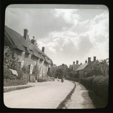 Row of thatched and timber-framed cottages on a curving road. | Courtesy of Warwickshire CC, Rugby Library Local Studies Collection. Warwickshire County Record Office reference PH827/5/39. Photographer Rev. E. Dew