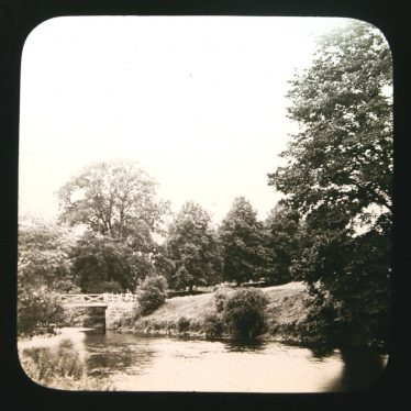 Footbridge with handrail over river with banks and trees. | Courtesy of Warwickshire CC, Rugby Library Local Studies Collection. Warwickshire County Record Office reference PH827/5/40. Photographer Rev. E. Dew