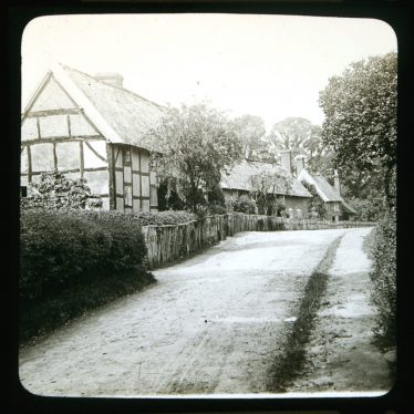 Row of thatched cottages with timber frame with hedge and fence bordering a road. | Courtesy of Warwickshire CC, Rugby Library Local Studies Collection. Warwickshire County Record Office reference PH827/5/41. Photographer Rev. E. Dew