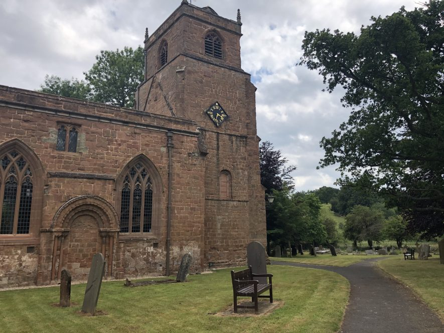 Sandstone brick church with path and yew trees on right hand side   Image courtesy of Laura Bradley